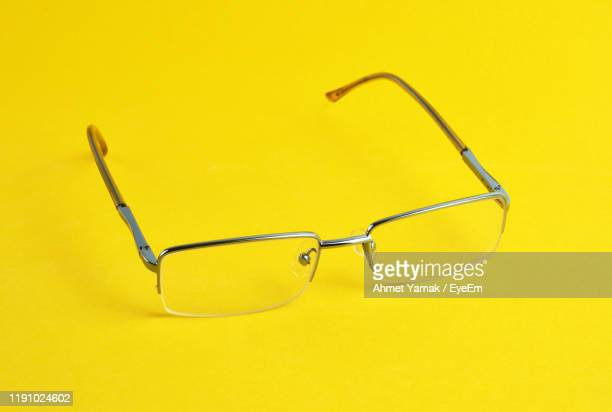 close-up of eyeglasses against yellow background - reading glasses stock pictures, royalty-free photos & images