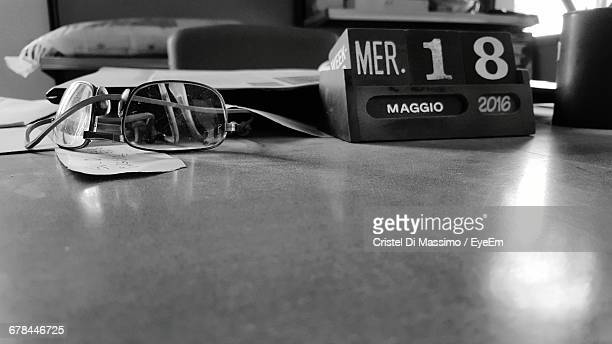 Close-Up Of Eyeglasses And Desk Calendar On Table