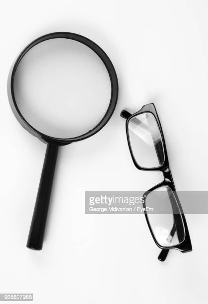 close-up of eyeglasses and magnifying glass against white background - reading glasses stock pictures, royalty-free photos & images