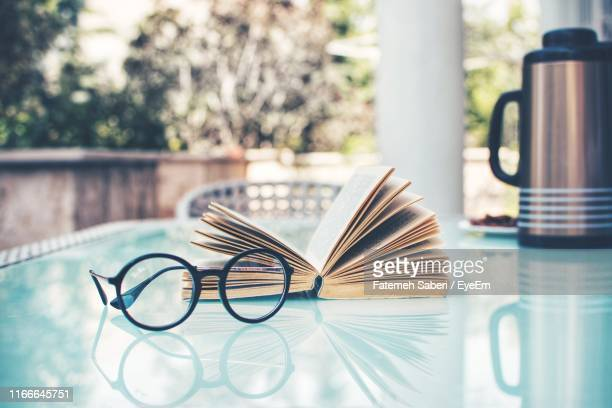 close-up of eyeglasses and open book on table at yard - reading glasses stock pictures, royalty-free photos & images