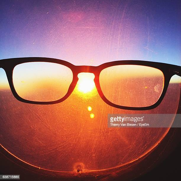 Close-Up Of Eyeglasses In Front Of Airplane Window At Sunset