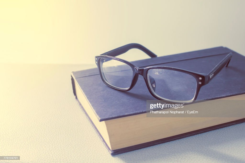 Close-Up Of Eyeglasses On Book At White Table : Photo