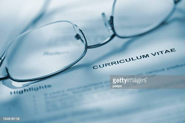 Closeup of eyeglasses on curriculum vitae.