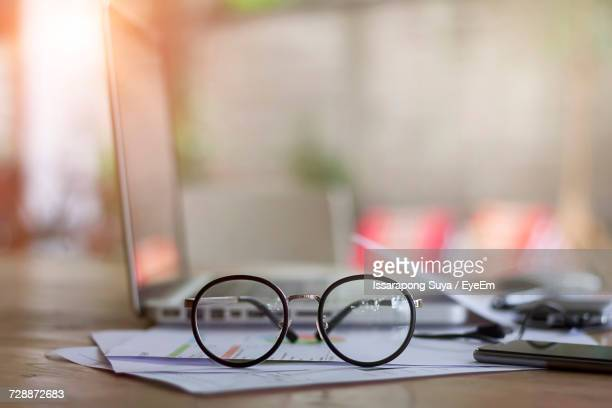 close-up of eyeglasses on desk - differential focus stock pictures, royalty-free photos & images