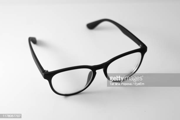 close-up of eyeglasses on gray background - black and white stock pictures, royalty-free photos & images