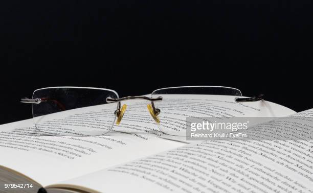 Close-Up Of Eyeglasses On Open Book Against Black Background
