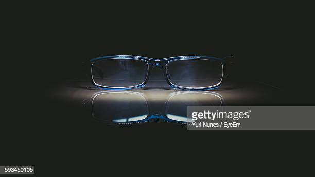 Close-Up Of Eyeglasses On Table Against Black Background
