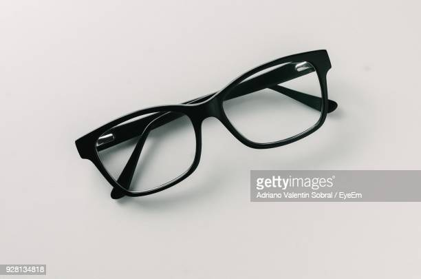 close-up of eyeglasses on table against white background - reading glasses stock pictures, royalty-free photos & images