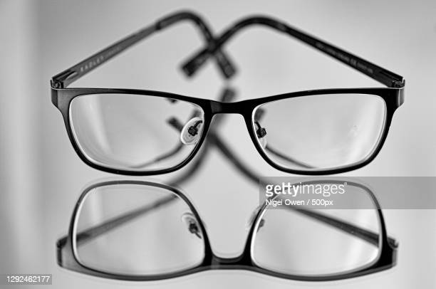 close-up of eyeglasses on table - nigel owen stock pictures, royalty-free photos & images