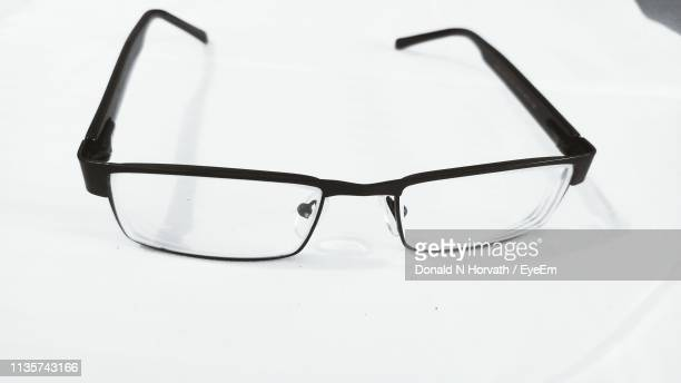 close-up of eyeglasses on white background - reading glasses stock pictures, royalty-free photos & images