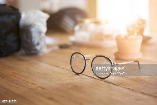 close-up of eyeglasses on wooden table - めがね ストックフォトと画像