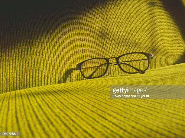 close-up of eyeglasses on yellow sofa at home - reading glasses stock pictures, royalty-free photos & images