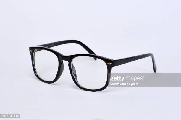 close-up of eyeglasses over white background - occhiali da vista foto e immagini stock