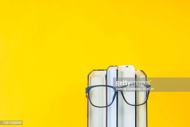close-up of eyeglasses with books against yellow background - still life not people stock photos and pictures