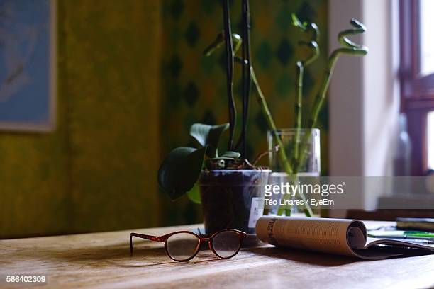 Close-Up Of Eyeglasses With Folded Book On Table With Flower Vase
