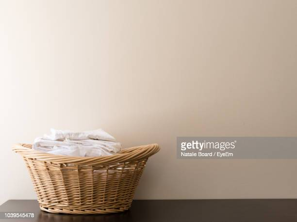 Close-Up Of Fabrics In Wicker Basket On Table Against Wall