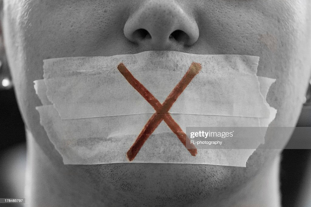 Close-up of face with tape over mouth and cross drawn on it : Stock Photo