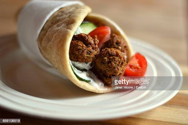 Close-Up Of Falafels In Wrap Sandwich On Plate