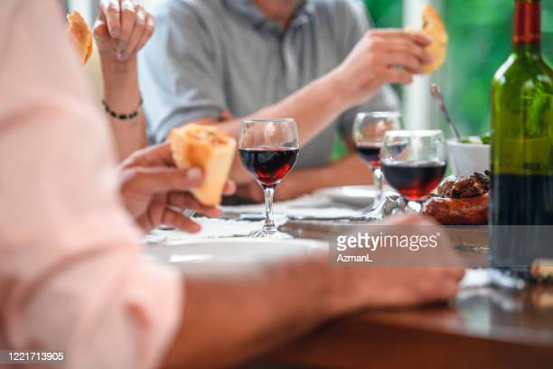 close-up of family members at dining table with red wine - empanada stock pictures, royalty-free photos & images