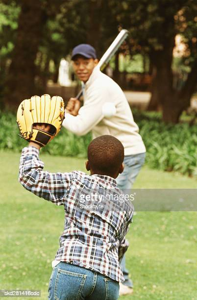 Close-up of father and son playing baseball (10-11)