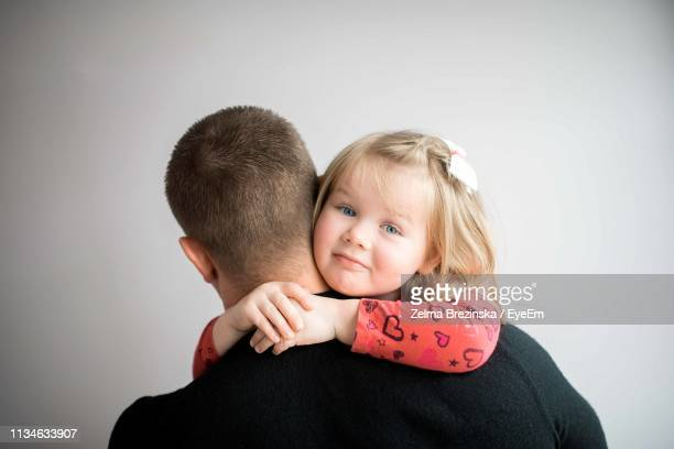 Close-Up Of Father Embracing Daughter Against Gray Background