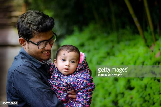Close-Up Of Father Holding Baby Daughter