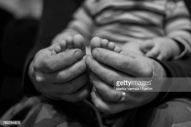close-up of father holding baby feet - vulnerability stock pictures, royalty-free photos & images