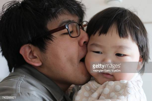 Close-Up Of Father Kissing Son At Home