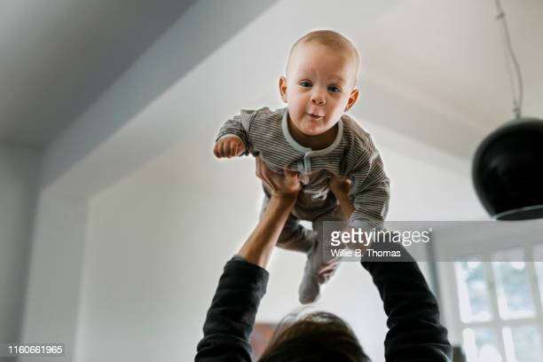 close-up of father lifting baby son - baby stock-fotos und bilder