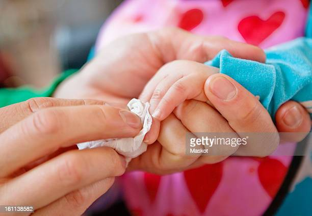 Close-up of father wiping daughter's (0-11 months) hands