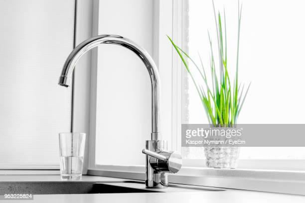 close-up of faucet by window at home - 水周り ストックフォトと画像