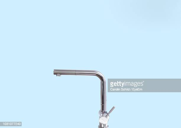 close-up of faucet over blue background - 蛇口 ストックフォトと画像