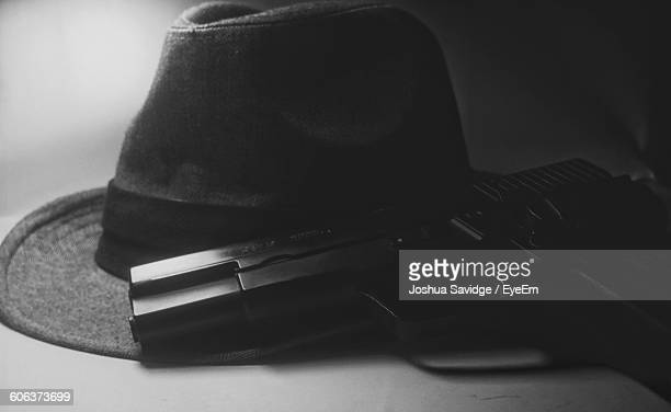 Close-Up Of Fedora And Gun On Table