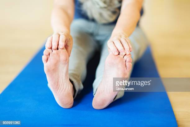 close-up of feet and hands of a woman bending down sitting - old lady feet stock pictures, royalty-free photos & images