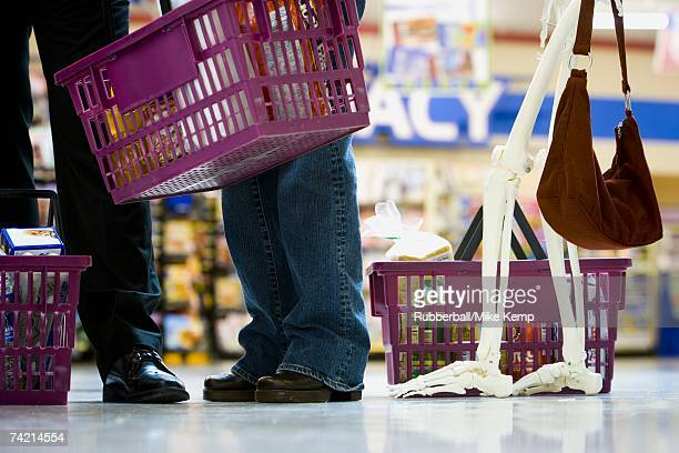 Closeup of feet and skeleton in grocery store line with shopping baskets