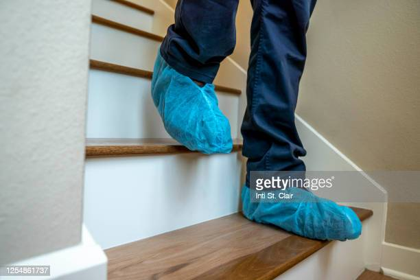 close-up of feet covered in shoe protectors walking down stairs - shoe covers stock pictures, royalty-free photos & images
