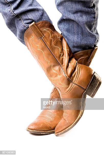 Close-up of feet in cowboy boots and jeans