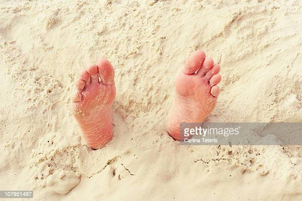 Close-up of feet in sand