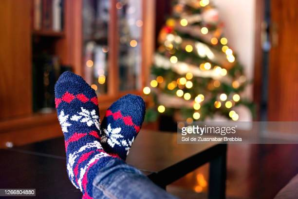 close-up of feet in warm winter socks near the christmas tree with its lights on - serene people stock pictures, royalty-free photos & images