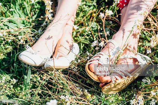 Close-up of feet of two girls in meadow