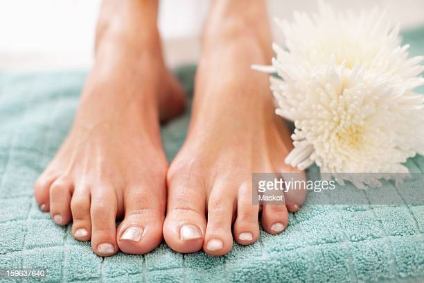 Close-up of feet of woman on towel in health spa
