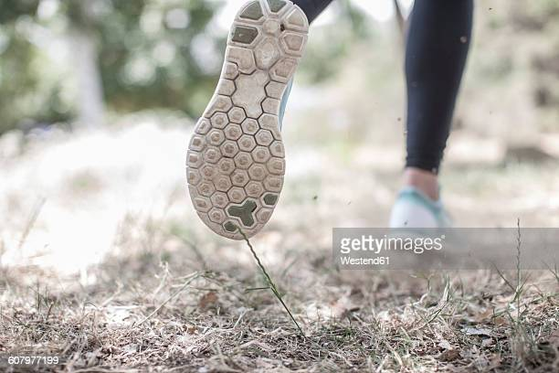 Close-up of feet of woman running in forest