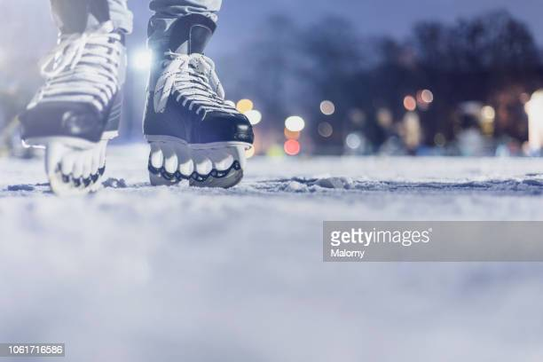 close-up of feet with ice skates on frozen lake. bokeh in the background. wintertime - ice skate stock pictures, royalty-free photos & images