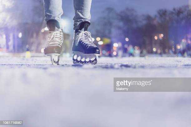 close-up of feet with ice skates on frozen lake. bokeh in the background. winter. - アイススケート ストックフォトと画像