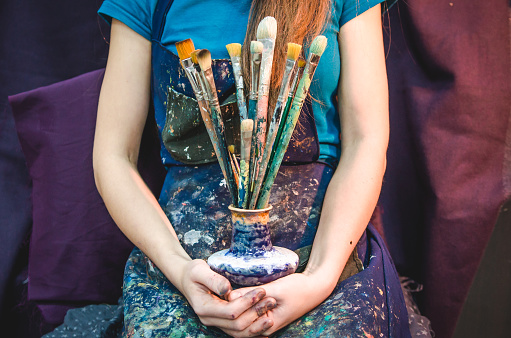 Closeup of female artist hands with paintbrushes 898696250