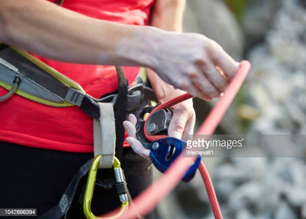 close-up of female climber with climbing equipment - klettern stock-fotos und bilder