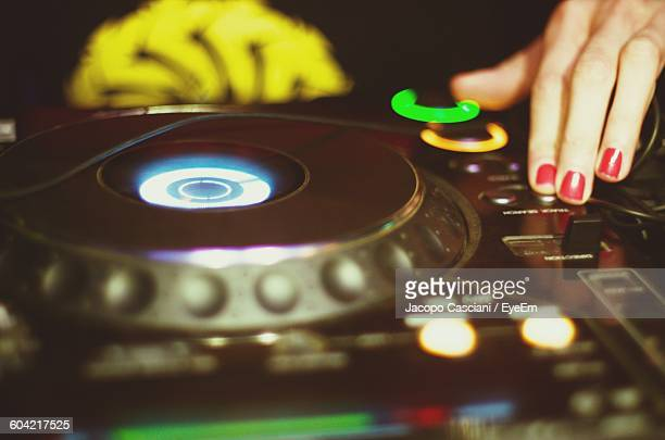 Close-Up Of Female Dj Playing Music At Club