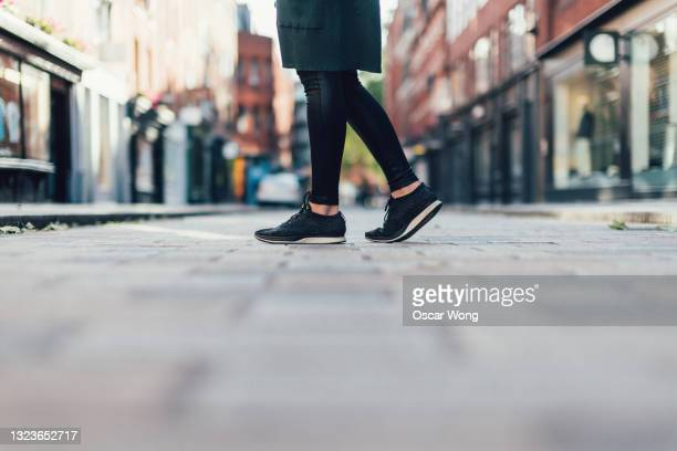 close-up of female feet walking down city street - human foot stock pictures, royalty-free photos & images