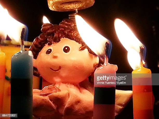 Close-Up Of Female Figurine By Illuminated Birthday Candles