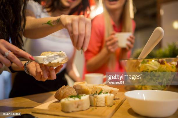 close-up of female friends preparing dinner together - spread food stock pictures, royalty-free photos & images